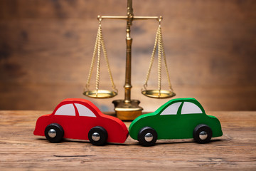 Two Red And Green Car In Front Of Justice Scale
