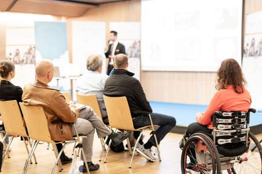 Rear view of nrecognizable woman on wheelchair participating in business conference talk. Business and entrepreneurship symposium. Speaker giving talk at business meeting. Audience in conference hall.