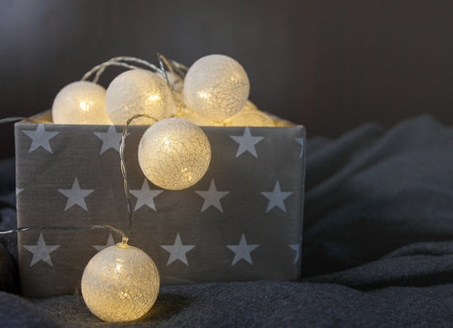 White cotton ball light garland in a grey basket wit stars sparkling at home. close up, bright lights, festive atmosphere. home decoration. New year and Christmas celebration concept