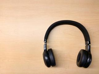 Black headphones on a light wood background.