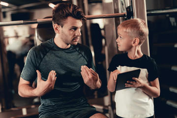 Father And Son In Gym. Information On Tablet.