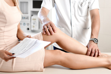 Doctor physiotherapist examining knee joint of woman suffering with knee cramp pain