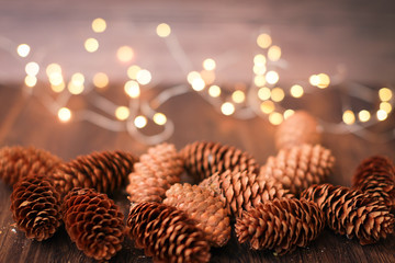 Christmas decoration in brown colors. Close up new year decor bumps and bokeh garland on wooden background.