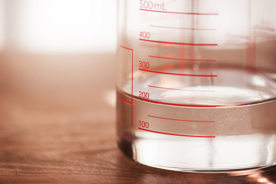 Measurements , measuring liquids. A measruing glassware or kitchen ware with water at 200ml line. Shallow depth of view.