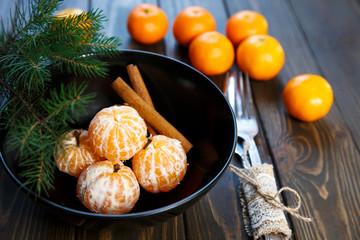 Ripe mandarine with leaves, tangerine mandarine orange in black bowl on wooden table background. Citrus fruits Mandarins in plate.  close up