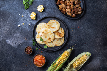 COLOMBIAN FOOD. Maize AREPAS and fried pork chicharron ans colombian tomato sauce. Top view. Black background