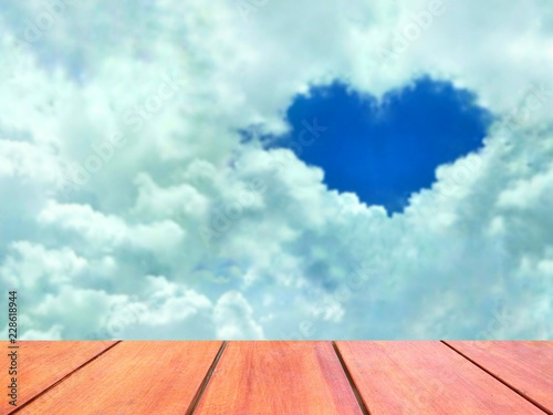 Empty wooden table on foreground and blur blue heart shaped in white