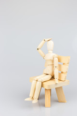 Wooden mannequin sitting on wood chair on white background.
