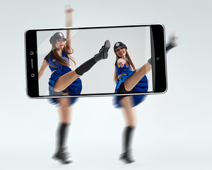 Two flexible women in erotic police uniform dancing. conceptual image with a smartphone, demonstration of device capabilities