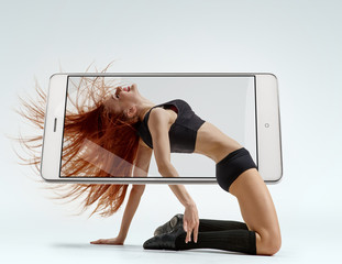 Photo of graceful woman contemporary dancer dancing on floor, concept virtual reality of the smartphone. going out of the device
