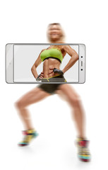 Sporty muscular woman doing squats, focus on belly. conceptual image with a smartphone, demonstration of device capabilities