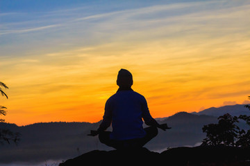 Silhouette of man doing yoga on top mountain at sunset or sunrise time
