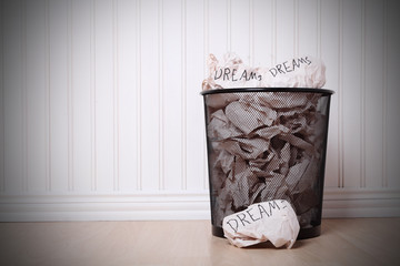 Concept for destroyed dreams. Wastepaper basket full of crumpled pages of paper which have the word DREAM written on them