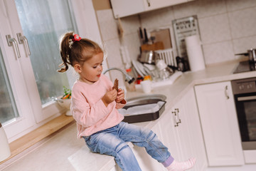 little girl eating chocolate in kitchen