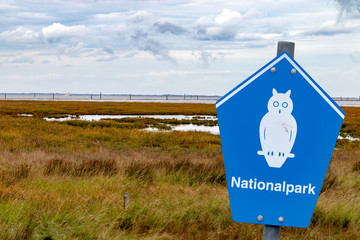 "blue sign of a german national parc on front of a coastline with german lettering ""nationalpark"" means national parc"