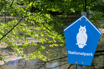 "Blue sign of a german national park in front of a small pond in the forestwith german lettering ""nationalpark"" means national parc"
