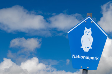 "Blue sign of a national park in germany in front of blue sky with german lettering ""nationalpark"" means national parc"