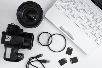 top view of dslr camera, lenses, photo equipment and laptop over white table