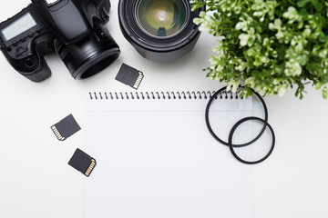 top view of photographer's workplace - camera, photography equipment and notepad over white table