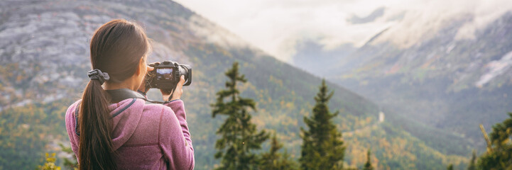 Travel tourist woman photographer taking pictures with video camera of nature landscape Alaska background, panoramic banner.