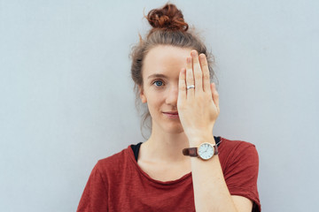 Pretty serious young woman covering her eye