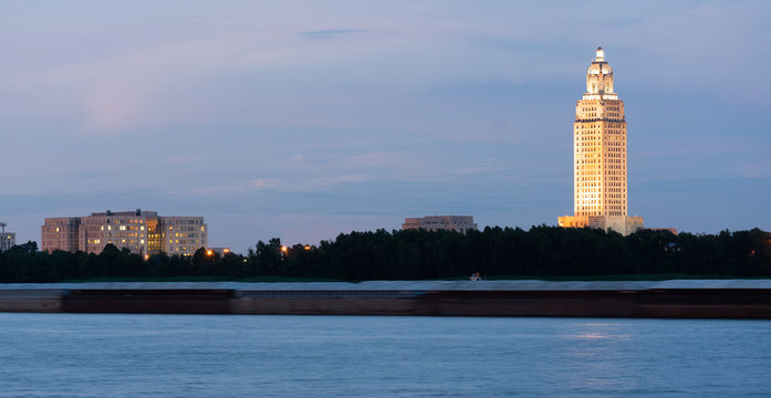 Night Falls While a Barge Travels Down Mississippi River Showing State Capital Building Baton Rouge