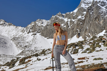 Model posing in a swimsuit and ski equipment in the mountains.
