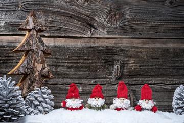 4 Weihnachtsmänner im Advent vor Holzwand