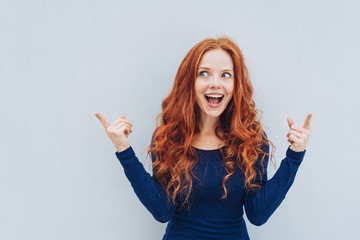 Excited young redhead woman pointing upwards