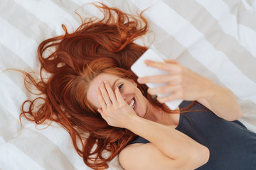 Cheerful woman lying in bed with mobile phone