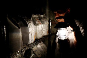 Kazuyuki Kitami, a city official of Yokosuka, holds a lantern as he visits a facility which keeps the unclaimed burial urns containing ashes of the dead in Yokosuka