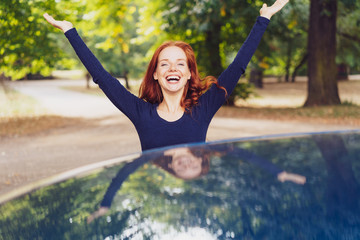 Happy young woman with arms raised in joy