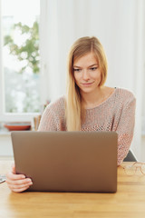 Young blonde woman using laptop at table