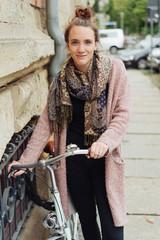 Stylish young student wheeling her bicycle