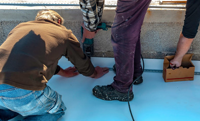 Worker with a heat gun is welding PVC sheets for waterproofing a terrace. Selective focus