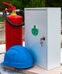 Safety equipment on a construction site: fire extinguisher, helmet, sanitary kit