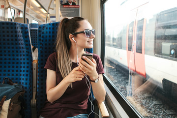 A young girl listens to a music or podcast while traveling in a train.