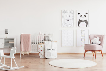 Stylish scandinavian nursery with white furniture and pink accents, cute poster on the white empty...