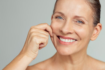 Beauty mature woman pulling perfect skin