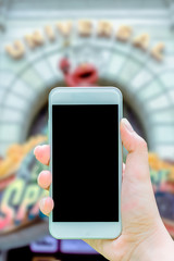 Mockup image of hand holding white cellphone with blank black screen that taking pictures theme park is blurred on background, vertical view.