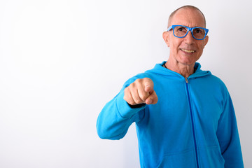 Studio shot of happy bald senior man smiling and pointing at cam