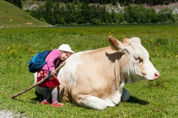 Little girl with backpack and walking stick cuddling a lying cow, Spitzingsee, Upper Bavaria, Bavaria, Germany, Europe