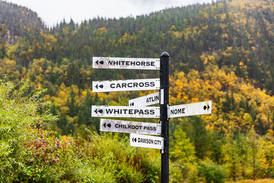 Alaska tourist street signs showing directions of different nearest tourism cities destination. Chilkoot, Whitehorse, Juneau, Skagway. Road sign in Skagway city.
