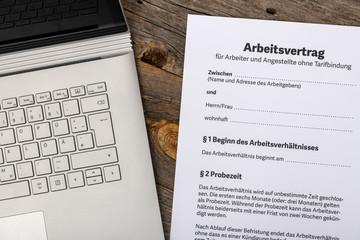Deutscher Arbeitsvertrag Tarif Vertrag für Angestellte und Arbeitgeber Closeup mit Laptop auf Holz Tisch zum Unterschreiben
