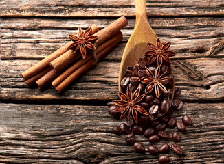 Coffee, anise, cinnamon  in wooden spoon on wooden background.