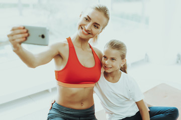 Mum And Daughter Are Doing Selfie On Gym Carpet.