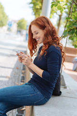 Young woman smiling as she reads a text message