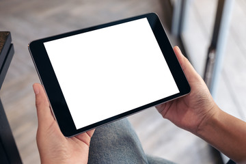 Mockup image of a woman sitting and holding black tablet pc with blank white desktop screen