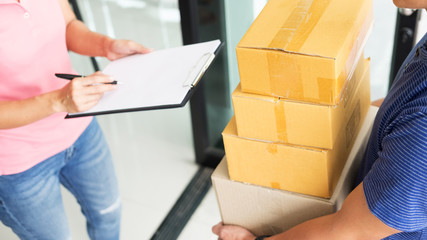 woman courier holding a parcel Shipping Mail appending signature signing delivery note after receiving package from delivery man.