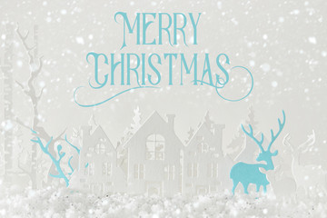 Magical Christmas paper cut winter background landscape with houses, trees, deer and snow in front of white background.